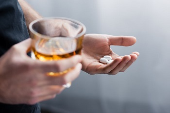 Man holds pills and a glass of whiskey